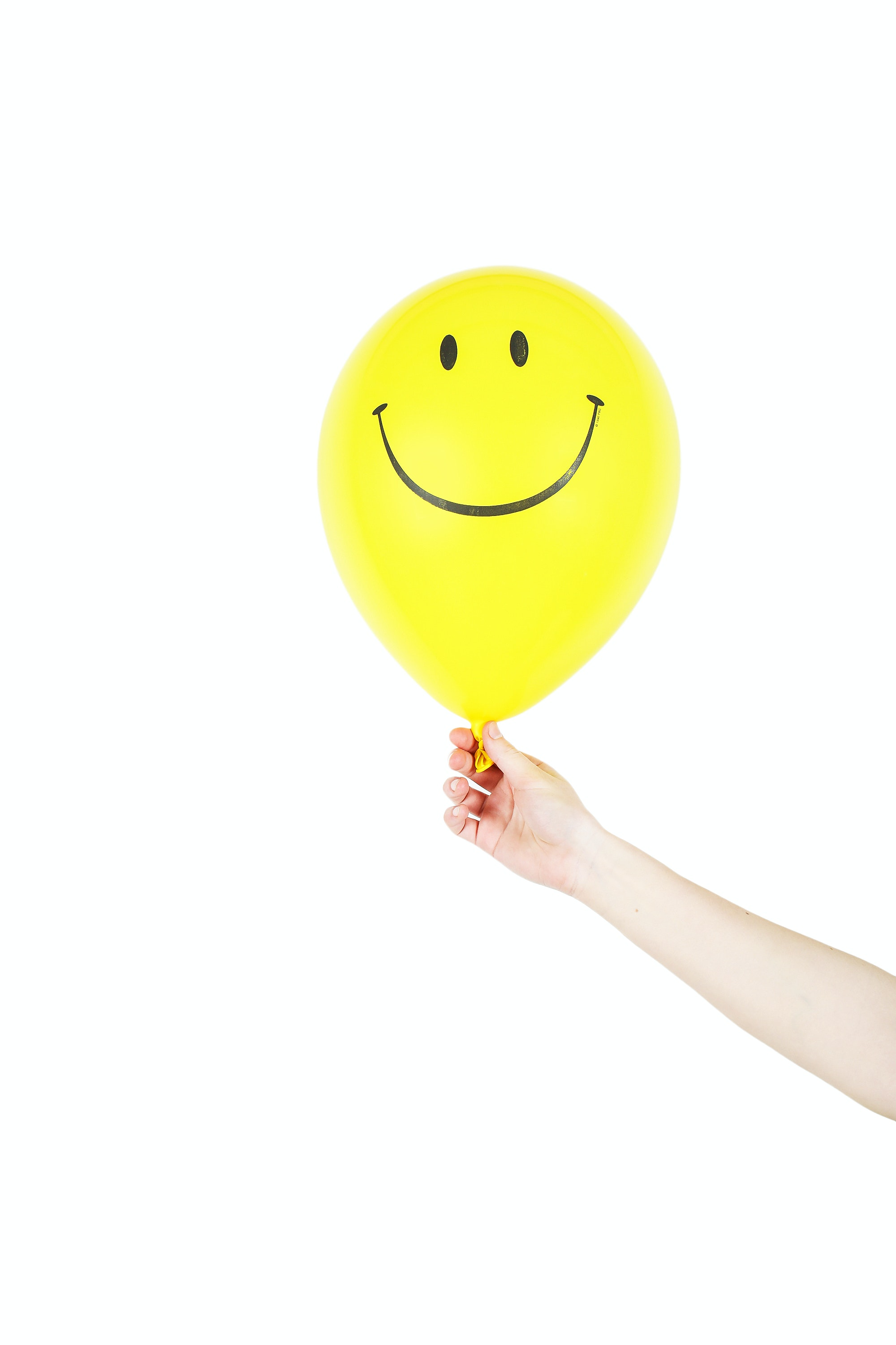 Someone holding a yellow balloon with a smiley face on it